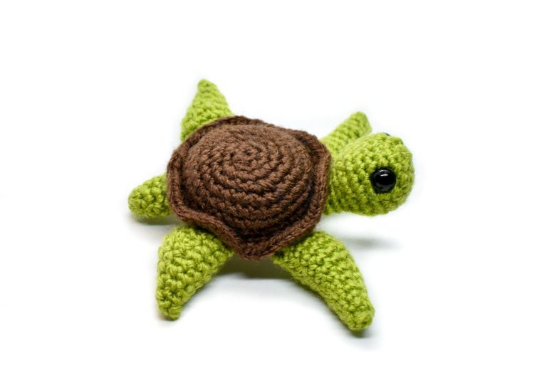 side view of a small crochet sea turtle toy with a white background