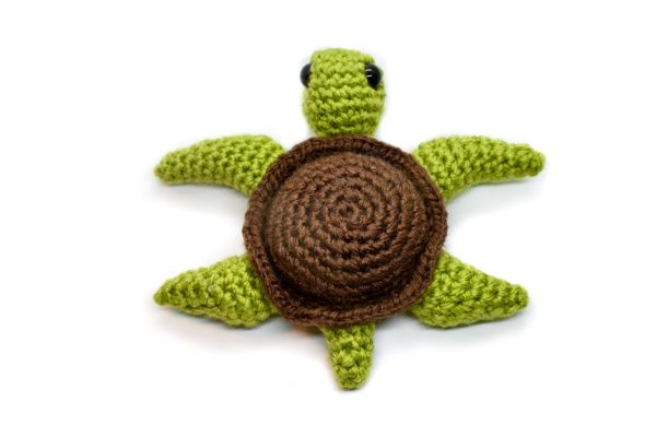 back view of a small crochet sea turtle toy with a white background