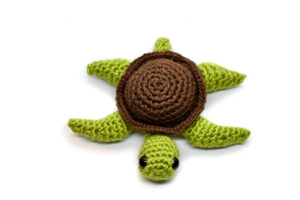 front view of a small crochet sea turtle toy with a white background
