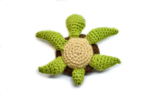 a small crochet sea turtle toy lying on its shell to show the placement of the flippers on the body, with a white background