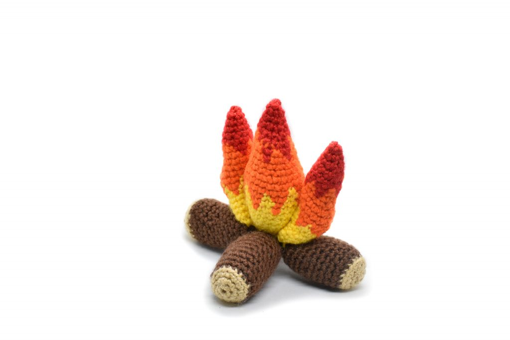 side view of a small plush crochet campfire against a white background
