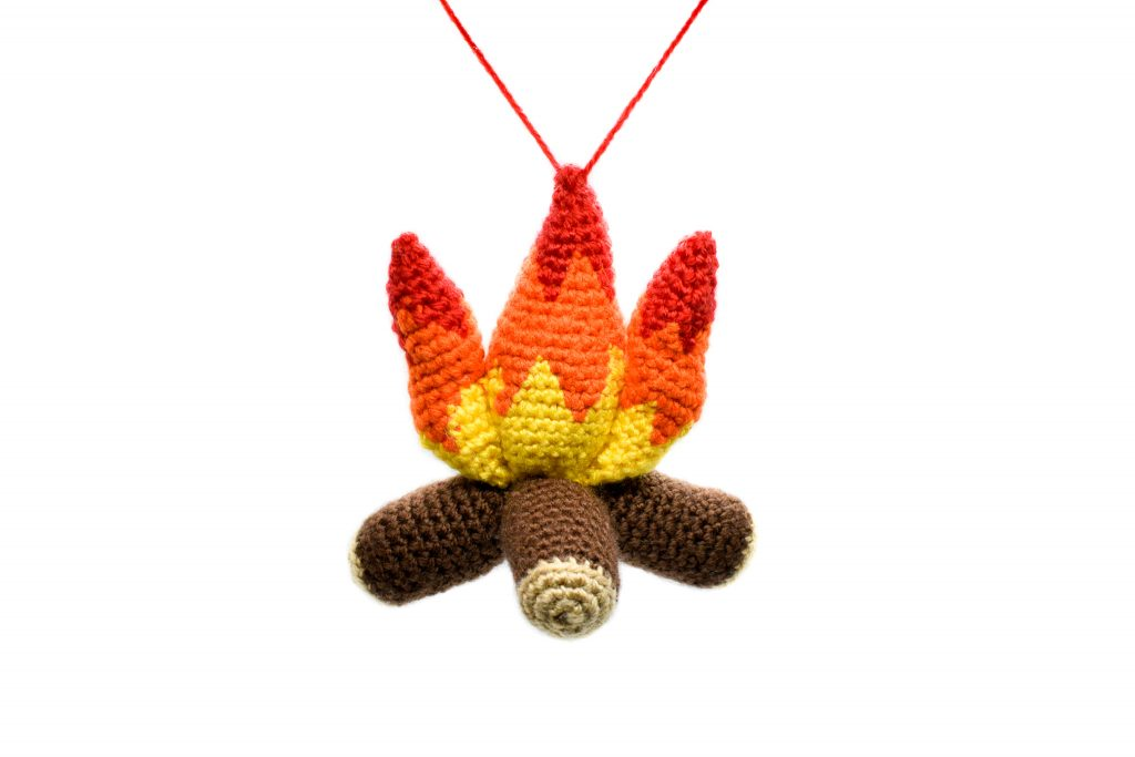 a small plush crochet campfire against a white background