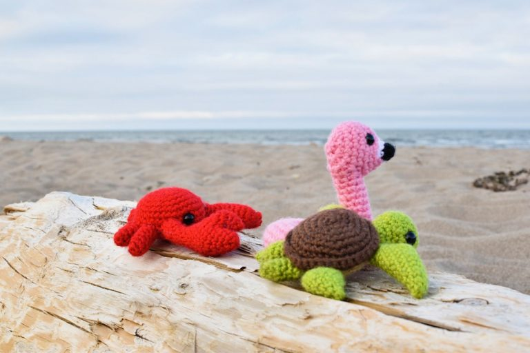 three small crochet toys sitting on a log at the beach - a flamingo floatie, a crab, and a sea turtle