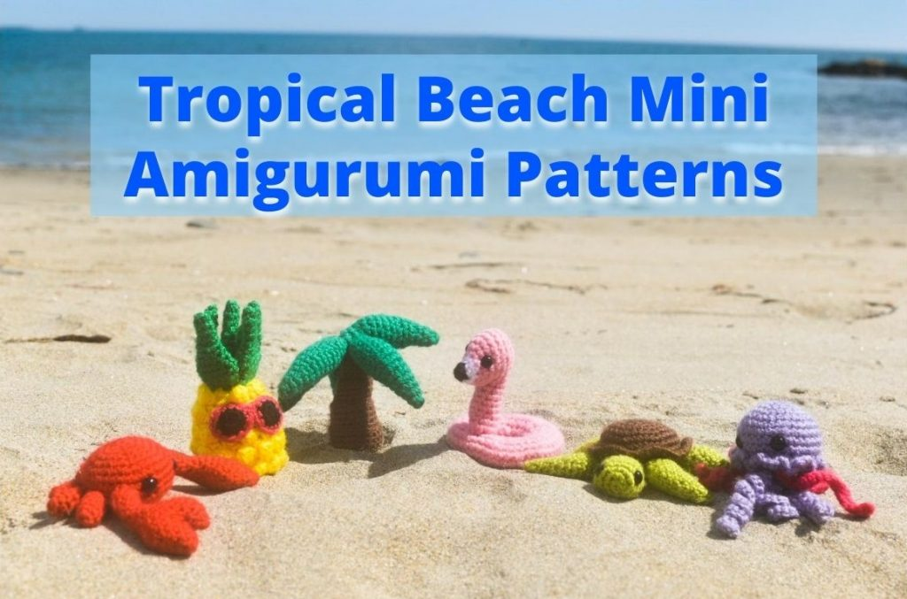 small crochet dolls of a crab, a pineapple, a palm tree, a flamingo floatie, a sea turtle, and a jellyfish sitting on a beach