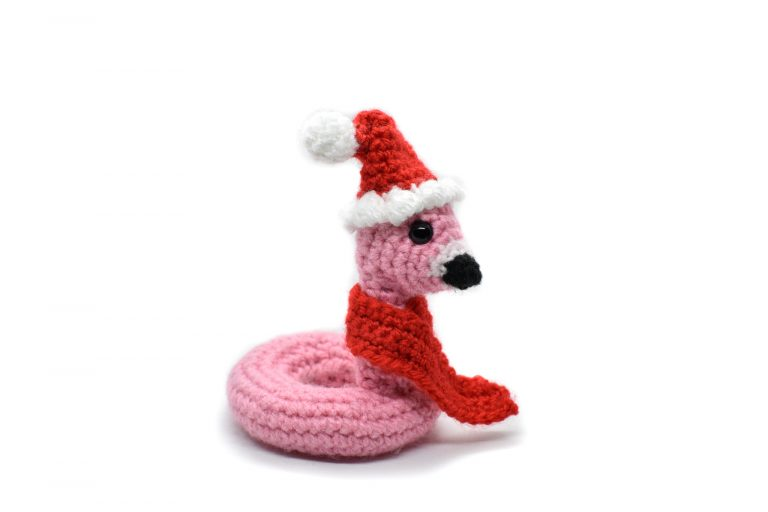 a small crochet flamingo floatie wearing a Santa hat and red scarf