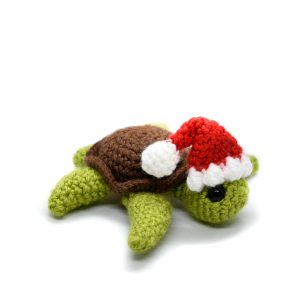 a small crochet turtle wearing a Santa hat