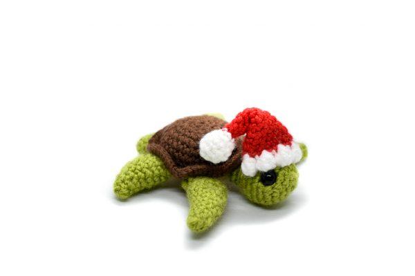 a small crochet turtle wearing a Santa hat