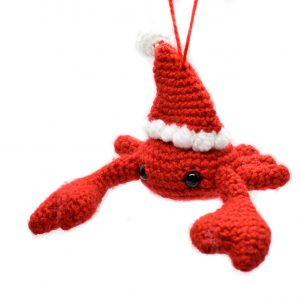 a small crochet crab wearing a Santa hat
