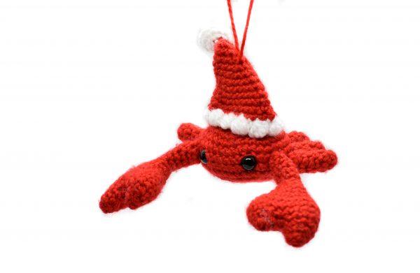 a small crochet crab wearing a Santa hat