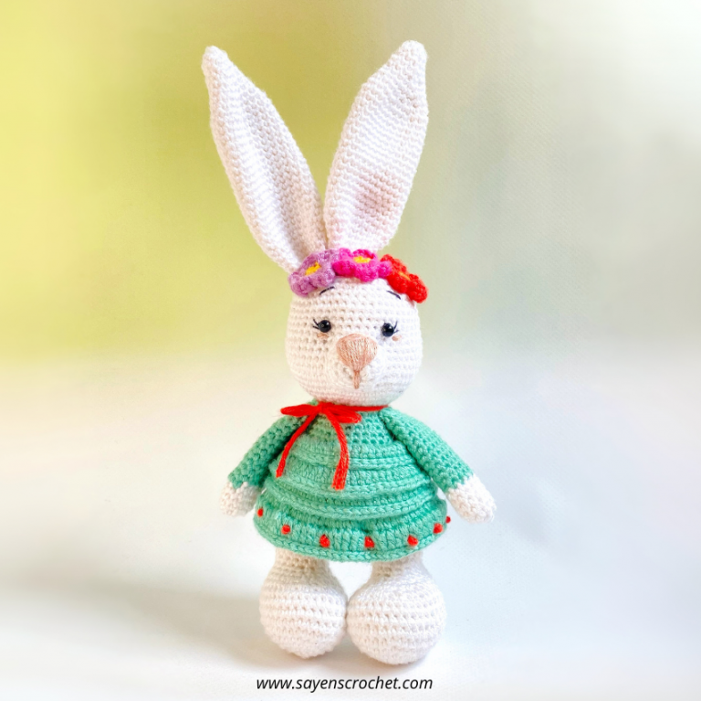 a white crochet bunny with flowers on her head, wearing a green dress