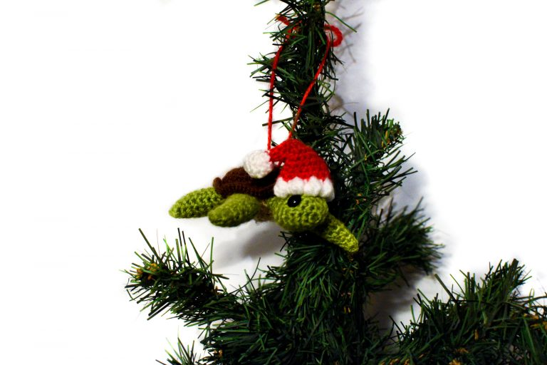 a small crochet sea turtle with a Santa hat, hanging from a Christmas tree