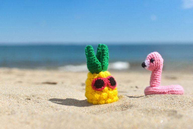 a small crocheted pineapple with sunglasses and a small crochet flamingo floatie sitting on a beach on a sunny day