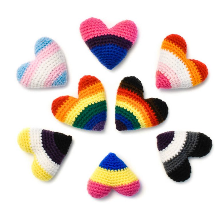 8 crochet hearts with pride colours. In the middle are two hearts in the rainbow Pride & Inclusive Pride flag colours, and around them are hearts depicting the Trans, Bisexual, Lesbian, Asexual, Pansexual, and Non-Binary flag colours.