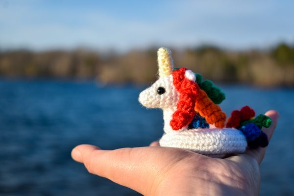 a small crochet unicorn floatie with rainbow coloured hair and tail, being held up in front of a lake