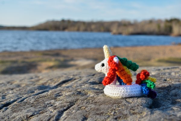 a small crochet unicorn floatie with rainbow coloured hair and tail, sitting on a rock next to a lake
