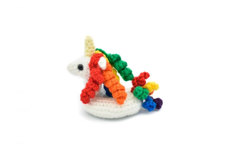 a small crochet unicorn floatie with rainbow coloured hair and tail