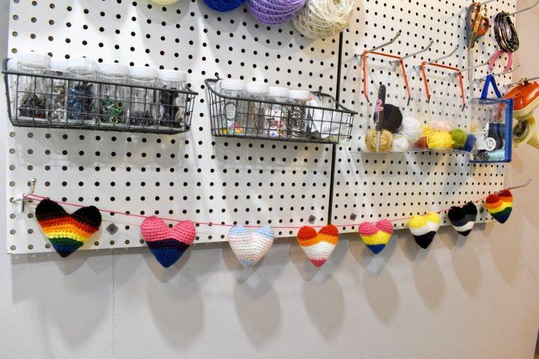 bottom of a pegboard holding various craft supplies. At the bottom, there are 8 crochet hearts in the Pride flag colours hanging from a string