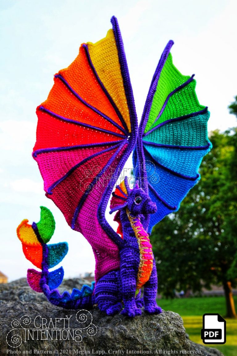 A large and detailed purple and pink crochet dragon with rainbow coloured wings spread above its body.