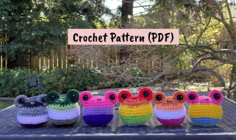 four simple crochet frogs made in various Pride flag colours, sitting in a row outside.