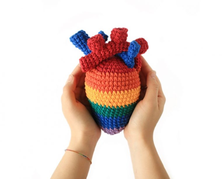 two hands holding a crocheted anatomical heart made in striped rainbow colours