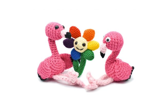two crocheted flamingos sitting against a white background. One of the flamingos is holding out a crocheted flower to the other flamingo. The flower has rainbow-coloured petals and a happy face.