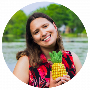 a picture of a young woman standing in front of a lake and holding a crochet pineapple