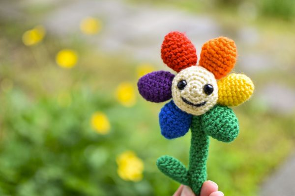 a small crochet flower with a light yellow middle, black plastic eyes and a smiley face. There are 6 solid-coloured petals arranged in rainbow order: red, orange, yellow, green, blue, and purple. The flower is being held up against a blurry background of grass and yellow flowers