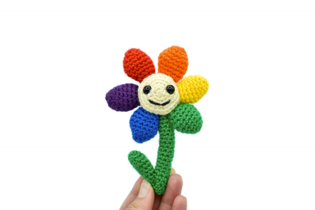 a small crochet flower with a light yellow middle, black plastic eyes and a smiley face. There are 6 solid-coloured petals arranged in rainbow order: red, orange, yellow, green, blue, and purple. The flower is being held up against a white background