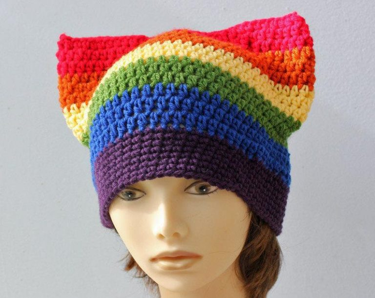 a crocheted hat with rainbow stripes on top of a mannequin's head. The top of the hat is sewn flat together to create the look of pointy ears. The stripes on the hat are in rainbow order with purple at the brim and red at the top