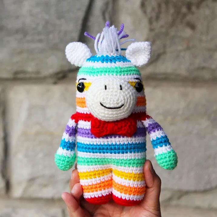 a crochet zebra with rainbow stripes