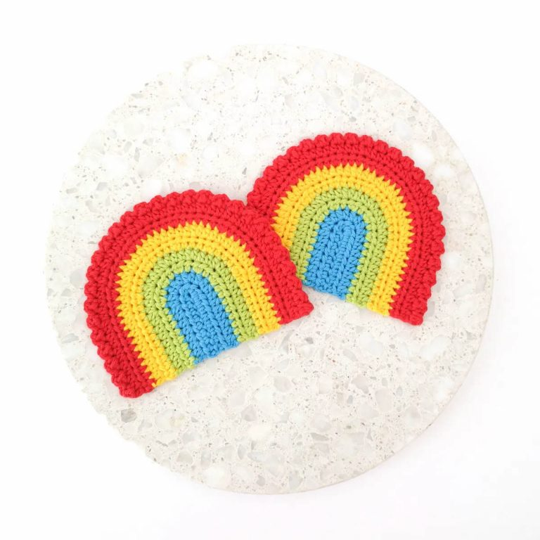Two rainbow shaped coasters on a white marble background