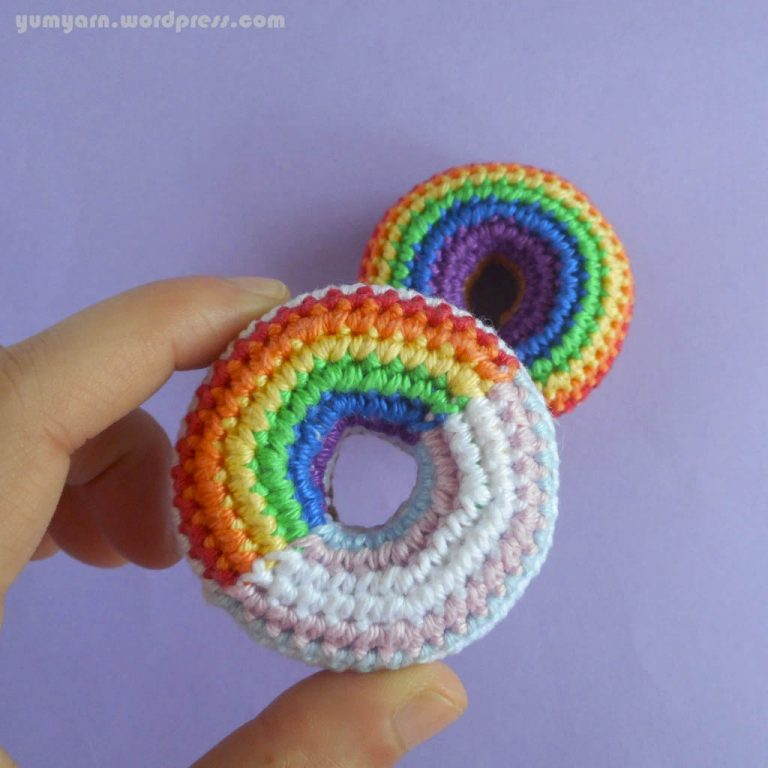 Two crochet donuts. One is crocheted in rainbow colours. The other is half rainbow and half Trans flag (blue, pink, and white)