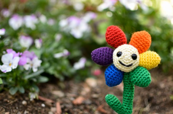 a small crochet flower with a light yellow middle, black plastic eyes and a smiley face. There are 6 solid-coloured petals arranged in rainbow order: red, orange, yellow, green, blue, and purple. The flower is being held up against a background of a garden with purple & white flowers