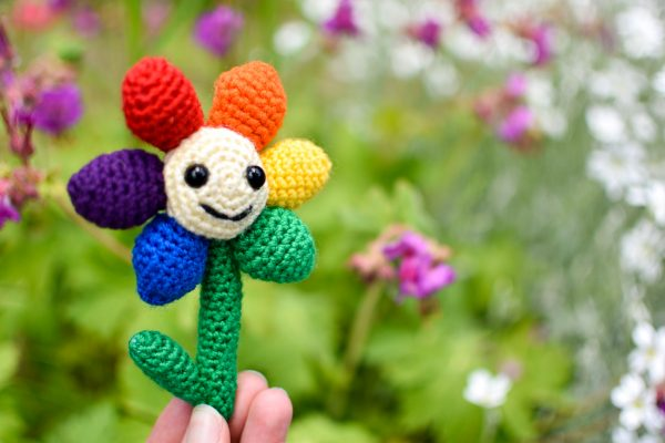 a small crochet flower with a light yellow middle, black plastic eyes and a smiley face. There are 6 solid-coloured petals arranged in rainbow order: red, orange, yellow, green, blue, and purple. The flower is being held up against a background of greenery and pink & white flowers