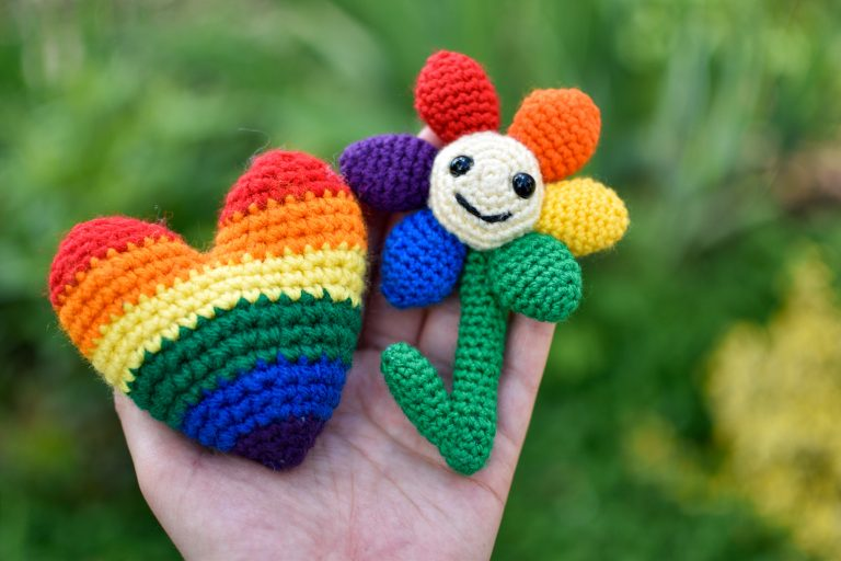 a hand holding a rainbow-coloured crochet heart and a small crochet flower with a light yellow middle, black plastic eyes and a smiley face. There are 6 solid-coloured petals arranged in rainbow order: red, orange, yellow, green, blue, and purple. The flower and heart are being held up against a background of greenery