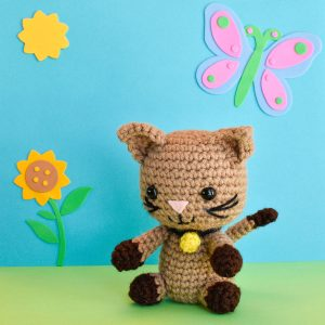 a crochet kitten doll against a blue and green backdrop with a cartoon sunflower, sun, and butterfly