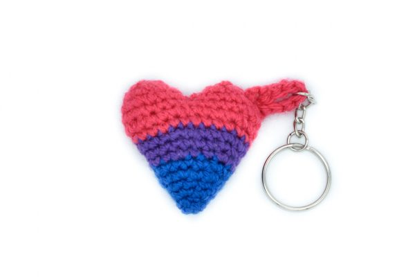 a small crochet heart keychain in the bisexual flag colours against a white background. From top to bottom, the colours are: pink, purple, blue