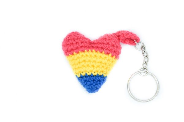 a small crochet heart keychain in the pansexual lag colours against a white background. From top to bottom, the flag colours are: pink, yellow, blue