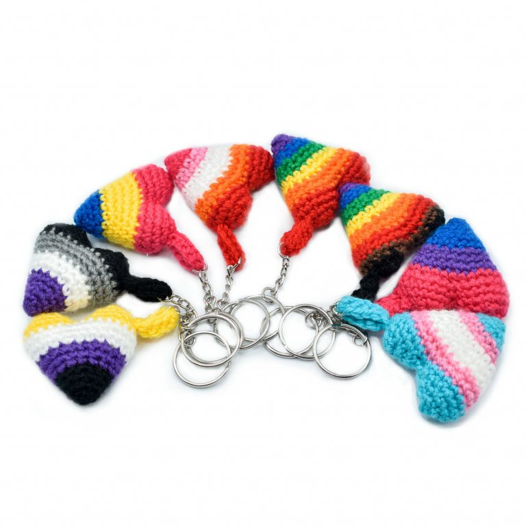 8 small crochet heart keychains with pride colours, arranged in a semi-circle. The pride flags are: Rainbow, Inclusive Rainbow, Trans, Bisexual, Lesbian, Asexual, Pansexual, and Non-Binary flag colours.