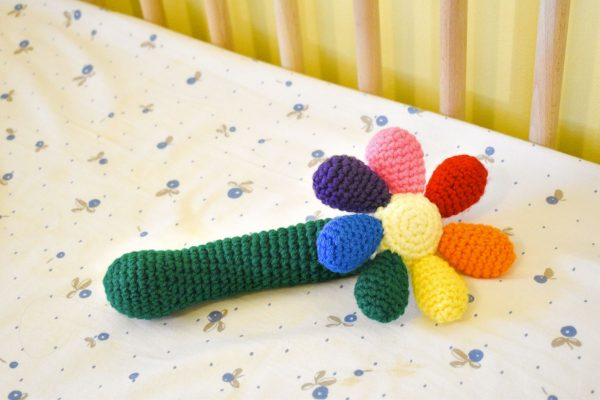 a crochet baby rattle in the shape of a flower. The handle is green, the centre of the flower is light yellow, and there are 7 round petals in red, orange, yellow, green, blue, purple, and pink. The rattle is lying in a baby crib