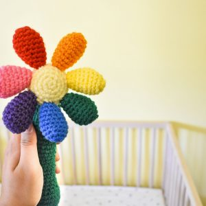a crochet baby rattle in the shape of a flower. The handle is green, the centre of the flower is light yellow, and there are 7 round petals in red, orange, yellow, green, blue, purple, and pink. The rattle is bring held up in front of a baby crib