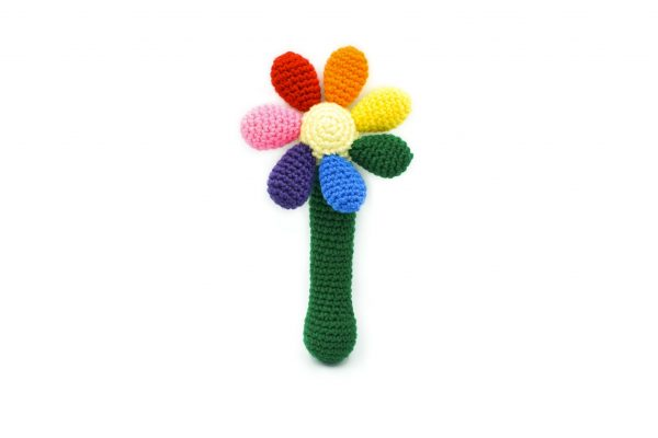 a crochet baby rattle against a white background. The rattle is in the shape of a flower. The handle is green, the centre of the flower is light yellow, and there are 7 round petals in red, orange, yellow, green, blue, purple, and pink.